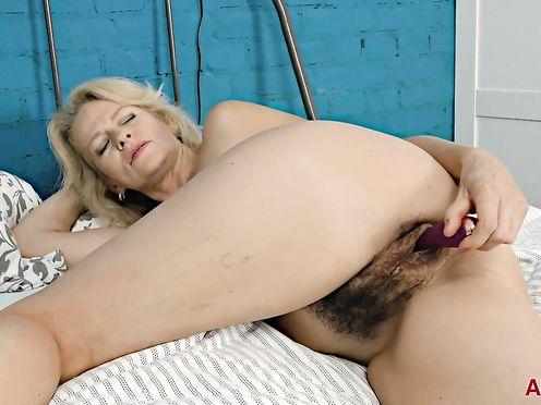 Зрелая блондинка в чулках мастурбирует волосатую киску секс игрушкой